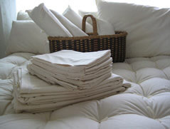 Organic Cotton Sheets Folded On Bed With Pillows, Neck Rolls And Comforter